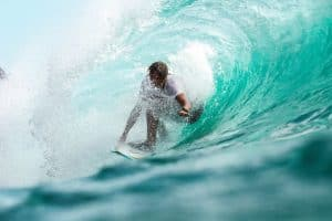 MAN SURFING ON A WAVE WITH A SURF WATCH ON